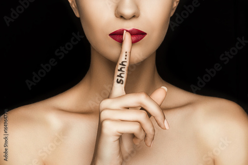 Photo cropped view of seductive woman with red lips showing shh symbol, isolated on bl