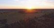 Aerial footage. Flying over the fields and forest at sunset with the sun's rays. Aerial drone shot.