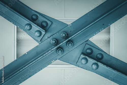 Blue construction beam forming an X  Halogen light background