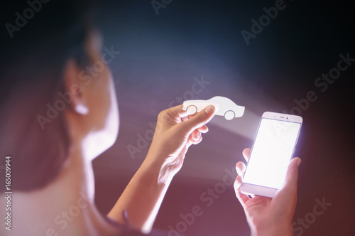 Image of a woman with a smartphone in her  hand. She holds car icon. Concept of modern technology in  transportation.