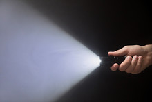 Black Flashlight With A Beam Of Light In Male's Hand Isolated From Right Side Of The Frame On Black Background Copyspace