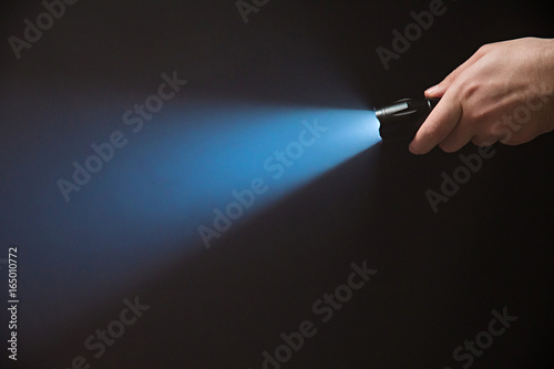 Male hand holding a led flashlight with a narrow blue beam on a