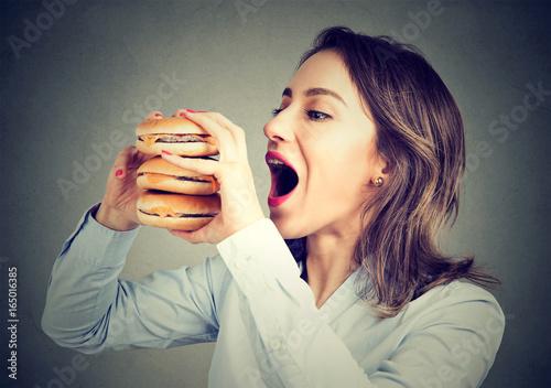 Cuadros en Lienzo Woman eating craving a double burger