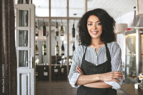 Fotografía  Young African American girl in apron standing with arms folded in restaurant