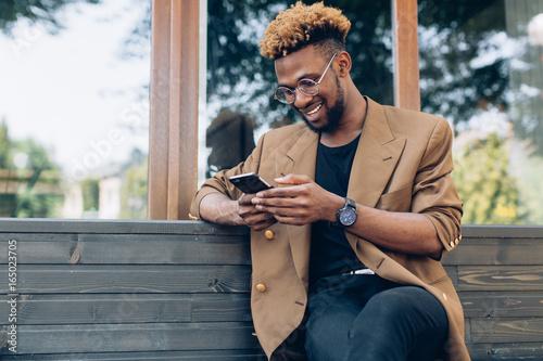 Zdjęcie XXL Portret African American człowieka w kurtkę i okulary z smartphone siedzi w pobliżu okna