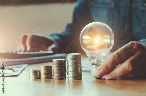 Photo  business accountin with saving money with hand holding lightbulb concept financi