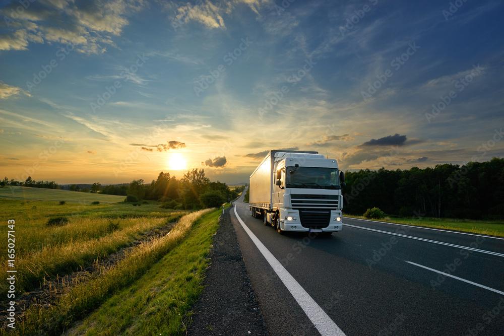 Fototapeta White truck driving on the asphalt road in rural landscape at sunset
