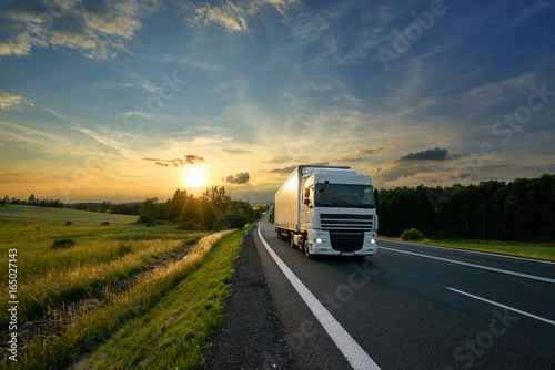 Fototapeta White truck driving on the asphalt road in rural landscape at sunset obraz