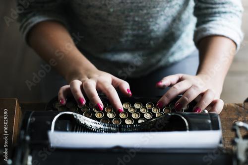 Photo  Woman typing vintage typewriter on wooden table