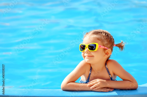 Smiling cute little girl in sunglasses in pool in sunny day. Fototapeta