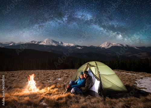 Poster Camping Young couple tourists having a rest in the camping at night, sitting near campfire, looking to the camera under beautiful starry sky and milky way. On the background snow-covered mountains