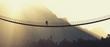 Leinwanddruck Bild - Man with backpack on a rope bridge