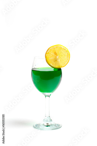 Staande foto Opspattend water Green cocktail in a glass with lemon on a white background