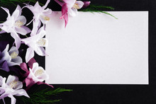 White Blank Condolence Card With Fresh Flowers On The Dark Background. Empty Place For A Text.