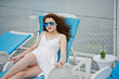 Portrait of a gorgeous young woman sitting on a lounger wearing her sunglasses on a lakeside.
