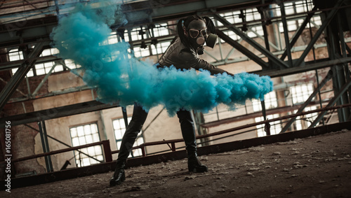 Fényképezés  A girl in a gas mask and latex posing with colored smoke at a ruined factory mag