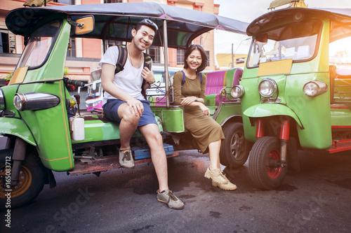 couples of young traveling people sitting on tuk tuk bangkok thailand Canvas Print