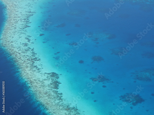 Aerial view of an atoll in Maldives with underwater coral reef seen through clear blue sea water. Maldives is a tropical island country in Indian Ocean consisted of more than a thousand islands.