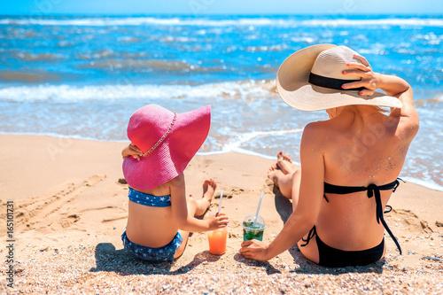 Plakat Tylny widok małej dziewczynki obsiadanie na plaży z macierzystymi i odświeżającymi napojami.