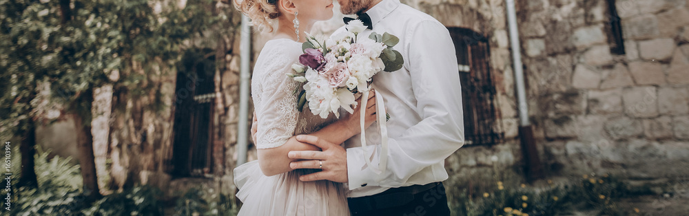Fototapeta stylish wedding couple with bouquet. modern bride and groom holding fashionable bouquet at old  castle. fine art wedding photo, romantic moment, long edge