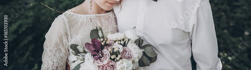 Obraz na płótnie stylish wedding couple with bouquet