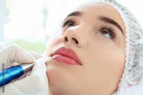 Cuadros en Lienzo Young woman having permanent makeup on lips in beautician salon