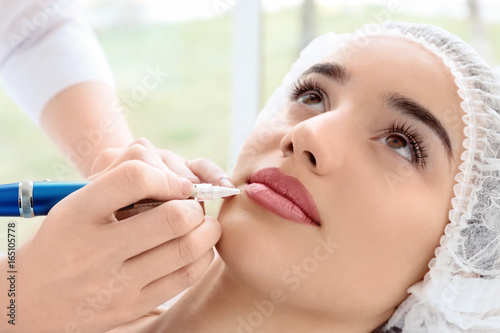 Fotomural Young woman having permanent makeup on lips in beautician salon