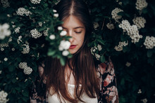 Sensual Calm Portrait Of Beautiful Hipster Woman In Blooming Bush With White Flowers Of Spirea. Boho Girl Sensual Portrait In Floral Modern Clothes In Greenery. Space For Text