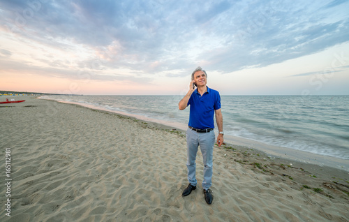 Fotografia  man talking on mobile on beach