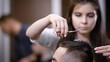 Female hairdresser making haircut with scissors and comb. Male customer sitting on the chair. Selective focus and close up view