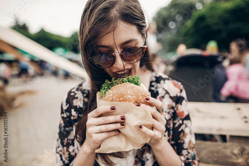 stylish hipster woman holding juicy burger and eating. boho girl with hamburger smiling at street food festival. summertime. summer vacation travel. space for text