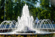 A Fountain Sparkling In The Evening Sun In The City Park.