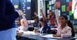Schoolkid raising their hands in classroom