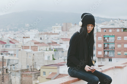 Young chinese woman listening music on tablet sitting on rooftop. Winter scene.