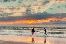 Boy And Girl Playing On The Beach During Sunset Watching A Kite Surfer
