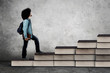 African student climbs stair shaped books