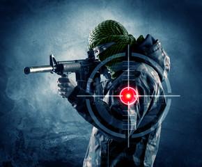 FototapetaMasked terrorist man with gun and laser target on his body
