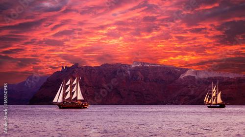 Foto op Plexiglas Crimson Sailboat in Santorini, Greece. Sailing ship navigate near an island in Cyclades. The photo is taken at sunset.