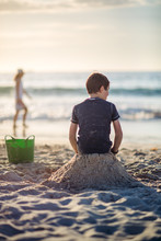 Boy Sitting On A Sand Castle At The Beach