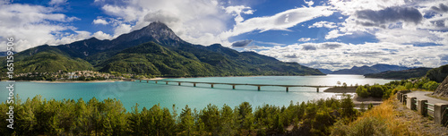 Fotobehang Alpen Panoramic view of Serre-Poncon Lake with Savines-le-Lac and its bridge with the Grand Morgon mountain peak in summer. Hautes-Alpes, Durance Valley, PACA Region, Southern French Alps, France