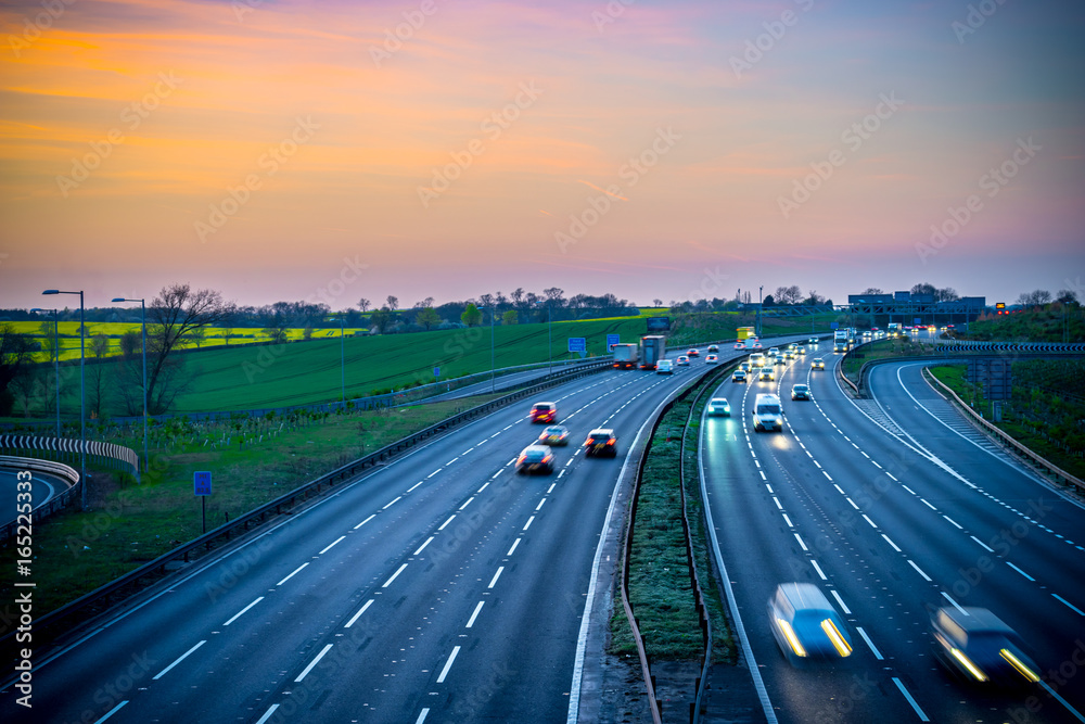 Fototapeta Colourful sunset at M1 motorway near Flitwick junction with blurry cars in United Kingdom