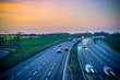 canvas print picture - Colourful sunset at M1 motorway near Flitwick junction with blurry cars in United Kingdom