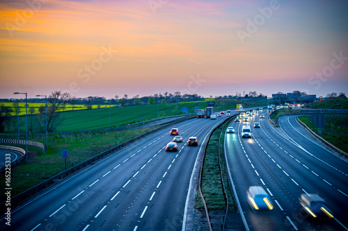 Obraz Colourful sunset at M1 motorway near Flitwick junction with blurry cars in United Kingdom - fototapety do salonu
