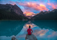Man In Red Sit On Rock Watching Lake Louise Morning Clouds With Reflections