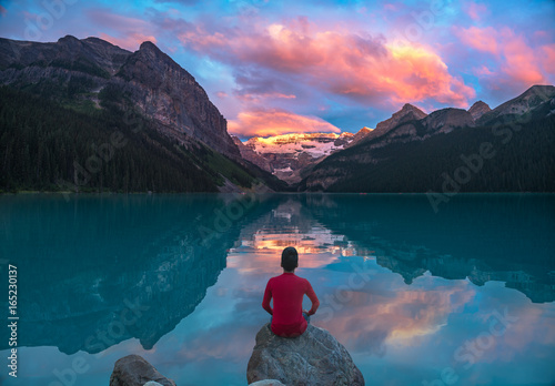 Spoed Foto op Canvas Canada Man in red sit on rock watching Lake Louise morning clouds with reflections