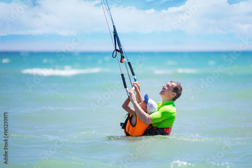 Male kite surfer teaching young boy how to ride kite