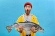 Studio shot of stylish young bearded fisherman in yellow raincoat and red hat looking in shock with jaw dropped, holding big sea-water fresh-caught fish in both hands, surprised with fine catch