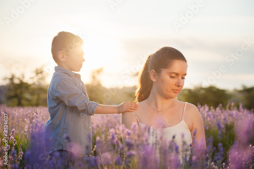 Fotografia  beautiful child laid his hand on the mother's shoulder among the lavender field