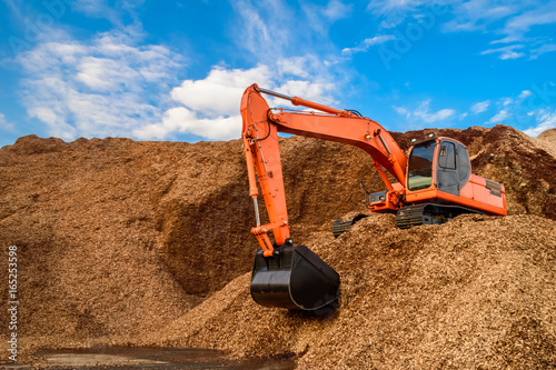 Valokuva  A load of wood chips handling by a powerful backhoe for loading onto trucks for exporting