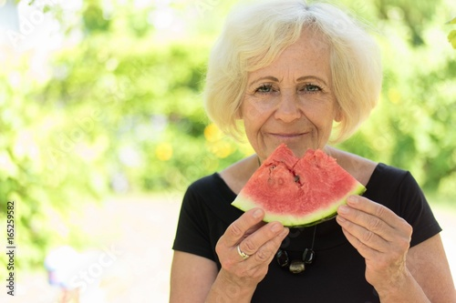 Mature woman eating watermelon.
